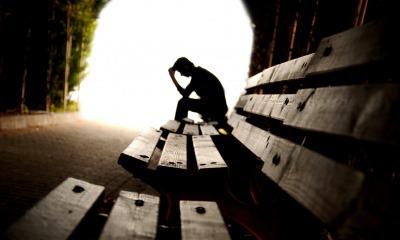 Pessoa deprimida em um banco de praça