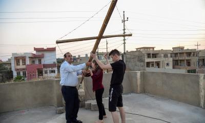 Essam, a esposa e o filho preparam a cruz