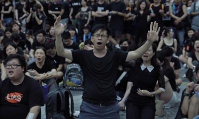 Manifestantes pró-democracia cantam