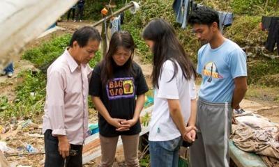 Missionário ora com pessoas