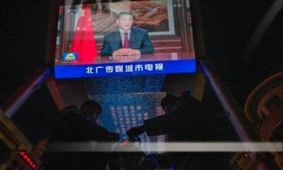 Guardas diante de tela com ditador Xi Jinping